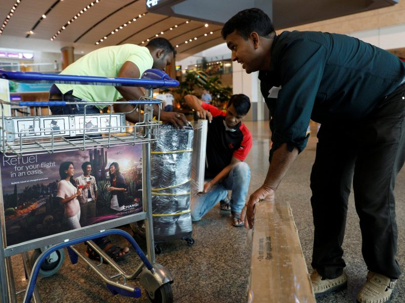 Mostaffa, a migrant worker who said he was returning to Dhaka after he was laid off by his employer, packs his luggages at Changi Airport in Singapore. Photo: Reuters/Edgar Su