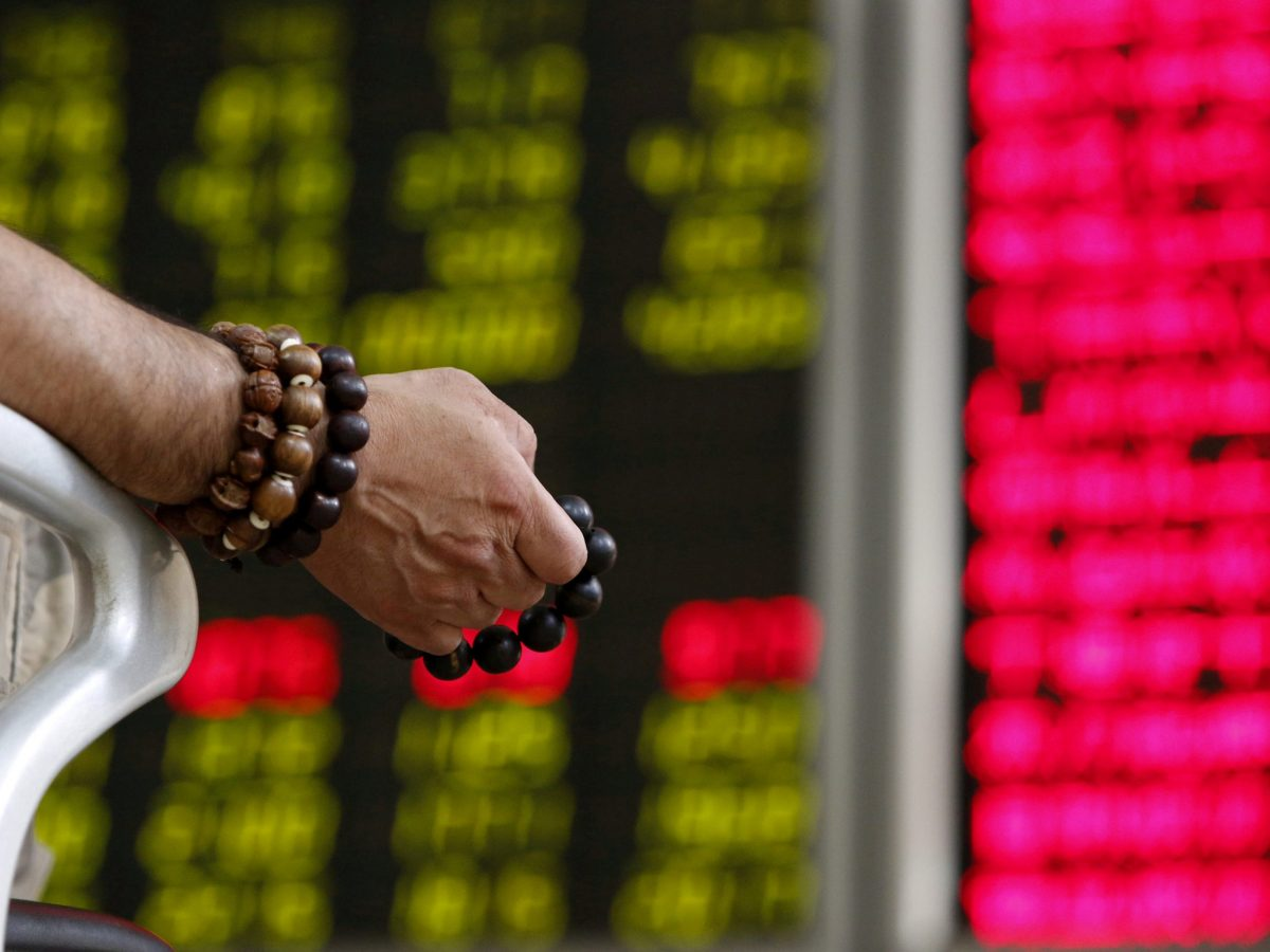 An investor holds onto prayer beads as he watches a board showing stock prices at a brokerage office in Beijing.     Photo: Reuters/Kim Kyung-hoon