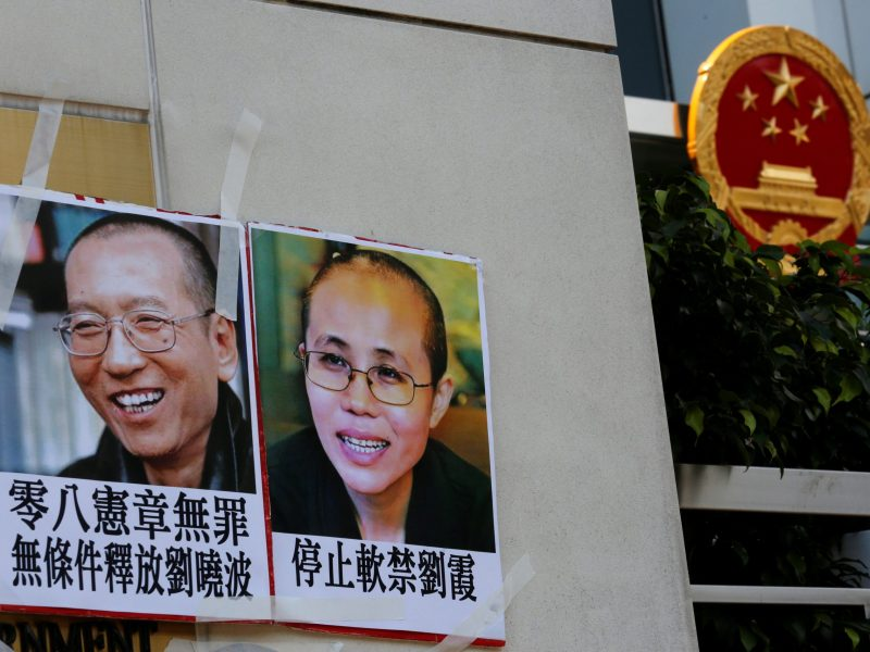Photos of rights activist Liu Xiaobo (left) and his wife Liu Xia were left by protesters outside China's Liaison Office in Hong Kong before the Nobel Peace Prize laureate's death from liver cancer last month. Photo: Reuters / Bobby Yip