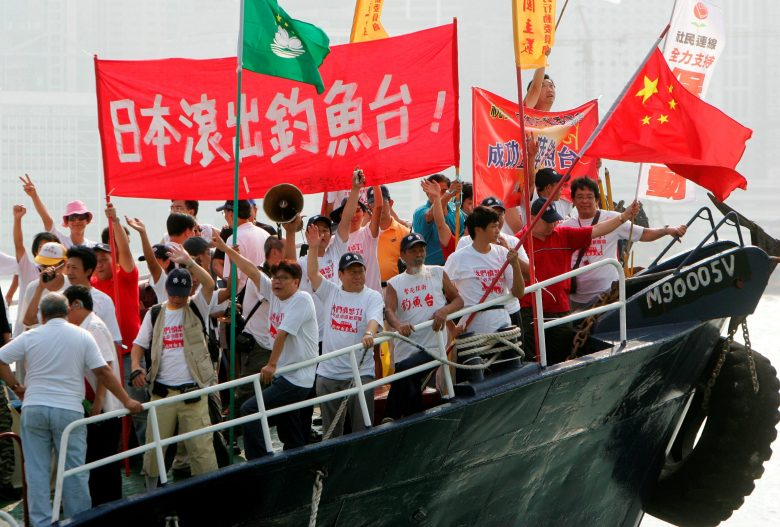 "Activists shout slogans and wave the Chinese flag aboard a vessel in Hong Kong, October 22, 2006.  Japan and China have sparred over a group of uninhabited islands known as the Senkaku Islands to Japanese and the Diaoyu Islands in China. The area is believed to lie near oil and gas reserves. In October 2006, a boat carrying activists from the Hong Kong-based Action Committee for Defending the Diaoyu Islands sailed within 20 km of the main island in the chain before they were warned off by a Japanese patrol boat. Chinese writing on a banner reads: ""Japan get out of the Diaoyu Islands"". Photo: Reuters/Paul Yeung"