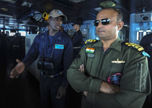 US Navy Ensign Muctarr Bah, speaks with Capt. Anil Komao from the Indian Navy, as they man the bridge during a replenishment-at-sea exercise. Photo: US Navy