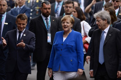 French President Emmanuel Macron, German Chancellor Angela Merkel and Italian Prime Minister Paolo Gentiloni chat in while in Sicily last month for the G7 summit. Photo: AFP/Filippo Monteforte