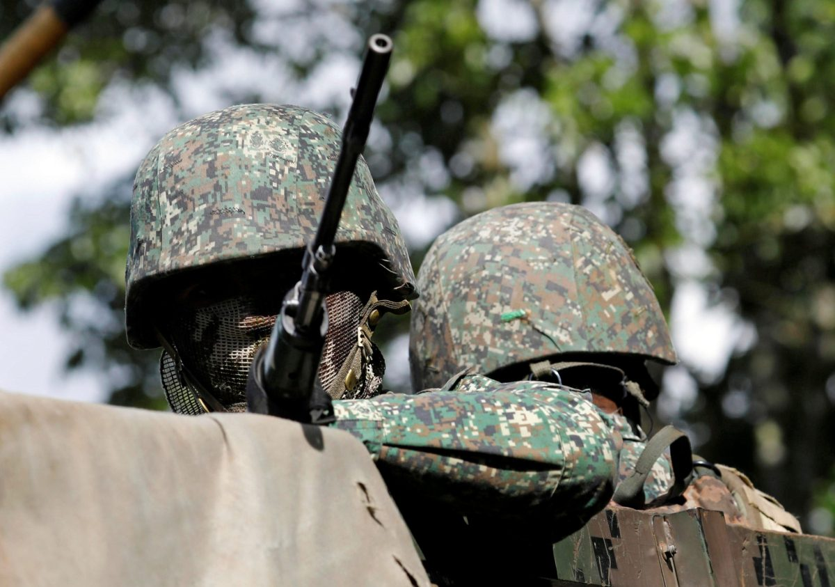 A masked government soldier holds a weapon aboard a military truck in Marawi City, southern Philippines May 30, 2017. Photo: Reuters/Erik De Castro
