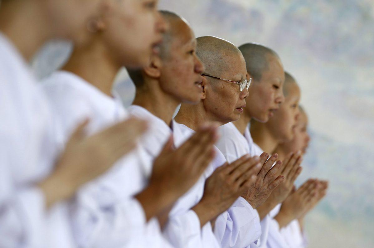 Buddhist nuns chant in the Sathira-Dhammasathan Buddhist meditation center in Bangkok. Photo: Reuters/Sukree Sukplang