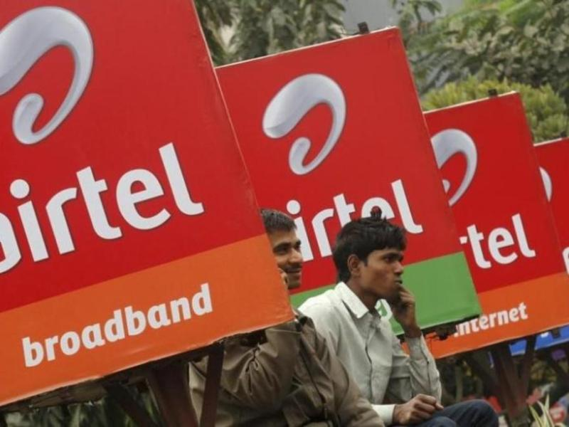 Men make phone calls as they sit near Bharti Airtel billboards in Kolkata. Photo: Reuters