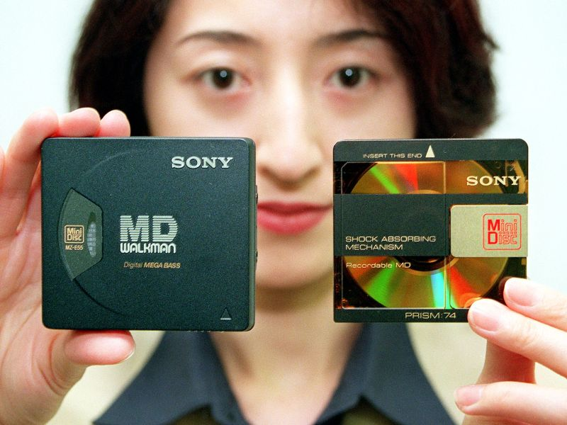 Sony employee Suzuyo Suzuki displays the MD Walkman MZ-E55 (left) and a mini-disc at the company's headquaters in Tokyo, on September 7, 1998. Photo: AFP / Toru Yamanaka