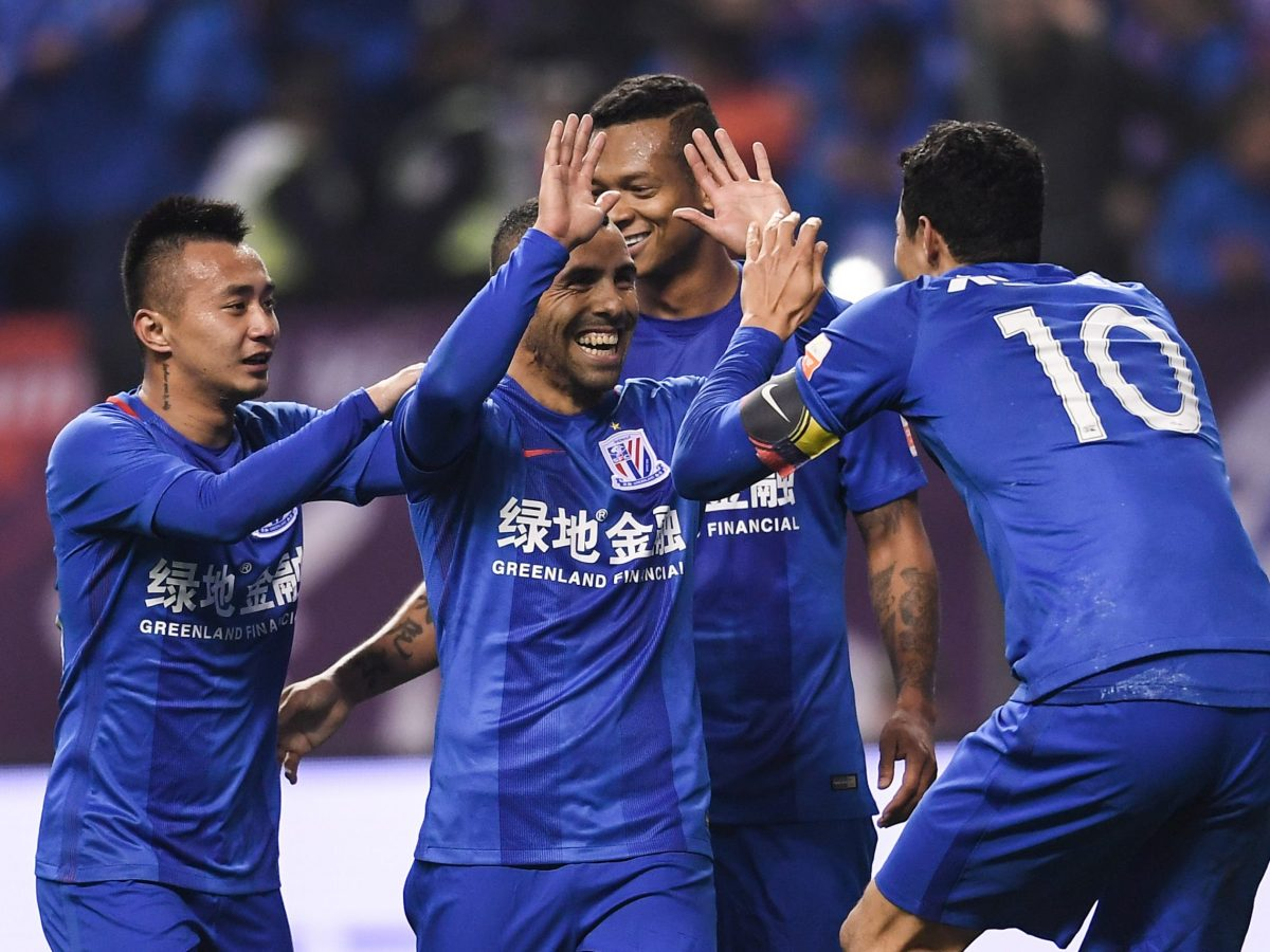 Carlos Tevez of Shanghai Greenland Shenhua Football Club, center, celebrates after scoring a penalty against Jiangsu Suning during their first round match in Shanghai in March this year. Photo: AFP.