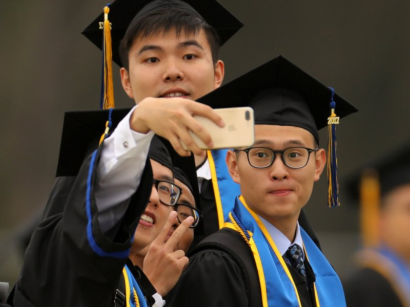 Students photograph themselves before the the Dalai Lama delivered the commencement speech to their 2017 graduating class at the University of California, San Diego. Photo: Reuters/Mike Blake