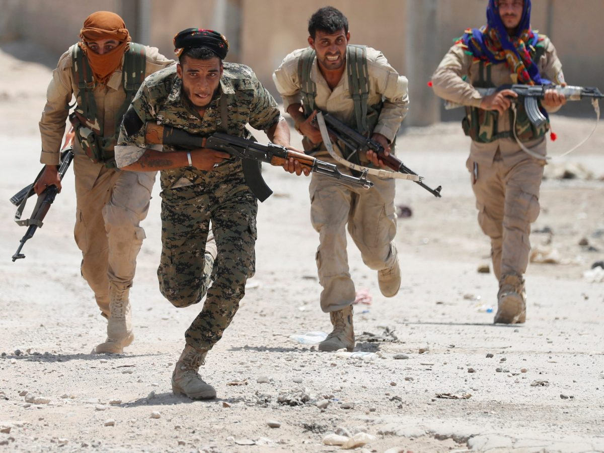 Kurdish fighters from the YPG run across a street in Raqqa, Syria July 3, 2017. Photo: Reuters / Goran Tomasevic