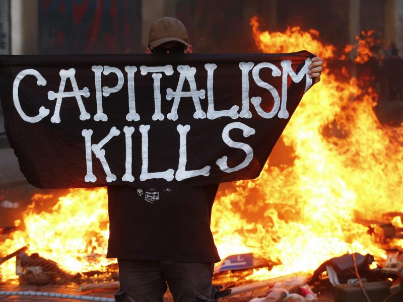 "A protestor holding up a ""Capitalism Kills"" sign. Photo: Reuters/Hannibal Hanschke"