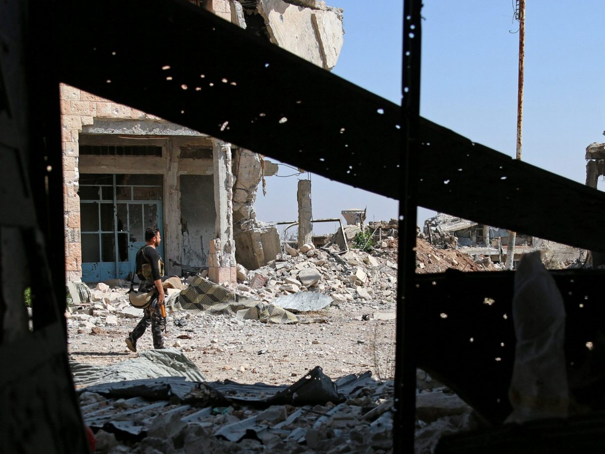 A Free Syrian Army fighter carries his weapon as he walks past damaged buildings in a rebel-held part of the southern city of Deraa, Syria, on July 9, 2017. Photo: Reuters / Alaa Al-Faqir