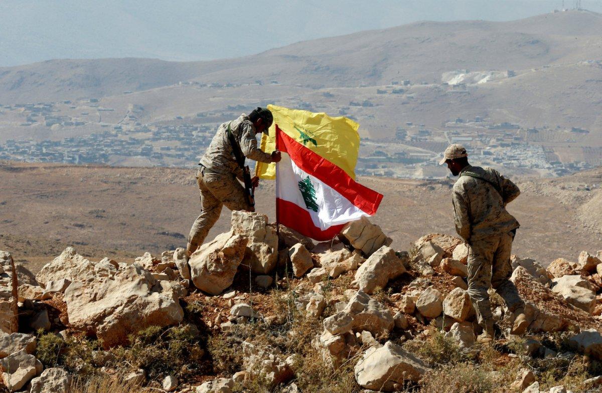 Hezbollah fighters plant Lebanese and Hezbollah flags at Juroud Arsal on the Syria-Lebanon border on July 25, 2017.  Photo: Reuters / Mohamed Azakir