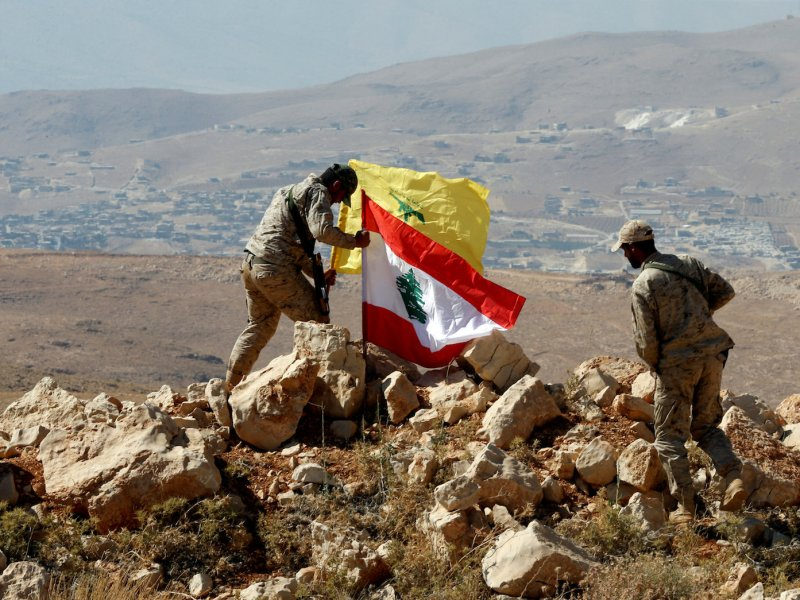 Hezbollah fighters plant Lebanese and Hezbollah flags at Juroud Arsal on the Syria-Lebanon border on July 25, 2017.  Photo: Reuters / Mohamed Azakir
