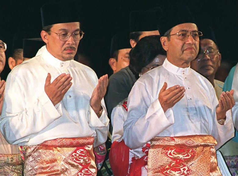 When we were young: Then Malaysian Prime Minister Mahathir Mohamad (R) and his deputy Anwar Ibrahim (L) pray during the United Malays National Organization party's 50th anniversary celebration in a 1996 file photo. Photo: AFP / Francis Silvan