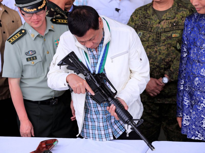 Philippine President Rodrigo Duterte inspects an automatic rifle at Clark Air Base, near Angeles City, on June 28, 2017. Photo: Reuters / Romeo Ranoco