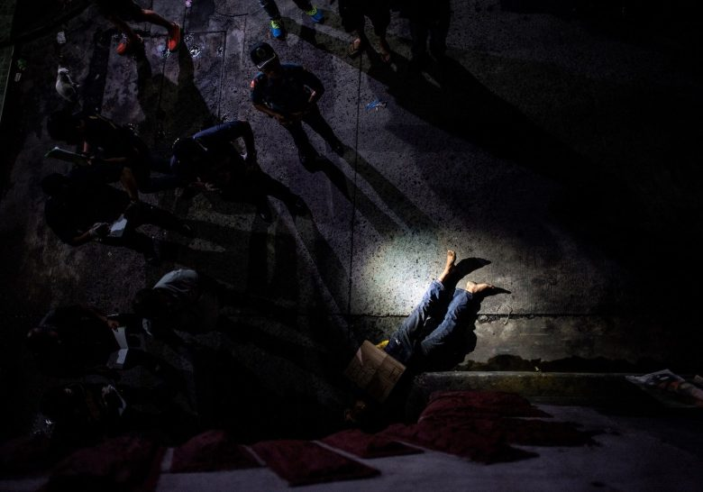 """EDITORS NOTE: Graphic content / (FILES) This file photo taken on July 8, 2016, shows police officers investigating a dead body of an alleged drug dealer, his face covered with packing tape in Manila.Duterte ends his first year as Philippine president on June 30, 2017 as a hugely popular leader, after taking Filipinos on a promised """"rough ride"""" of drug war killings and foreign policy U-turns. / AFP PHOTO / NOEL CELIS / GRAPHIC CONTENT"""