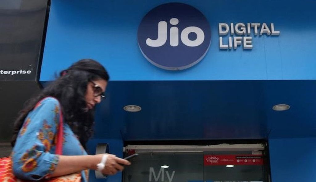 A woman checks her phone as she walks past a mobile store of Reliance Industries' Jio telecoms unit in Mumbai. Photo: Reuters