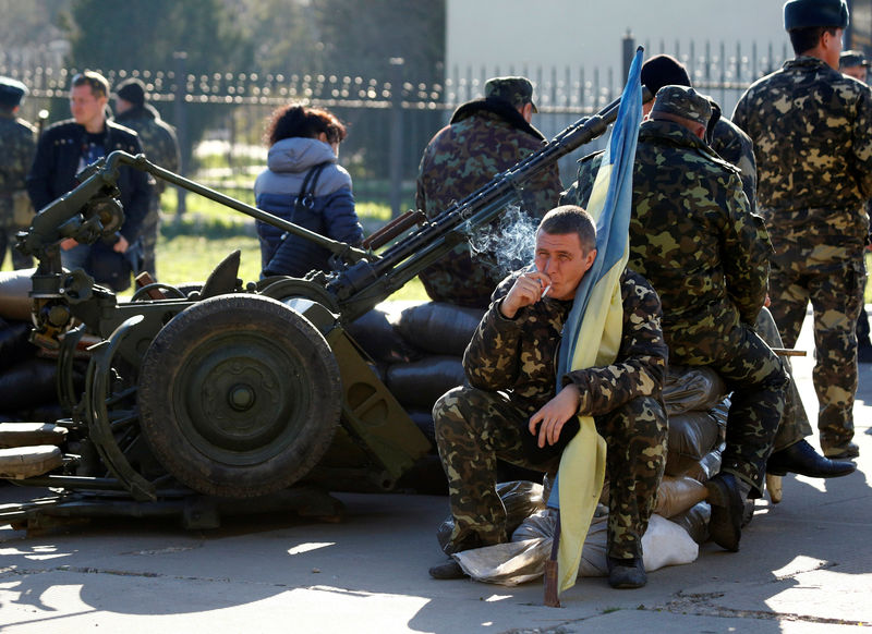 A Ukrainian serviceman holds a flag of Ukraine and smokes at a military base in the Crimean town of Belbek, Ukraine. Photo: Reuters/Shamil Zhumatov