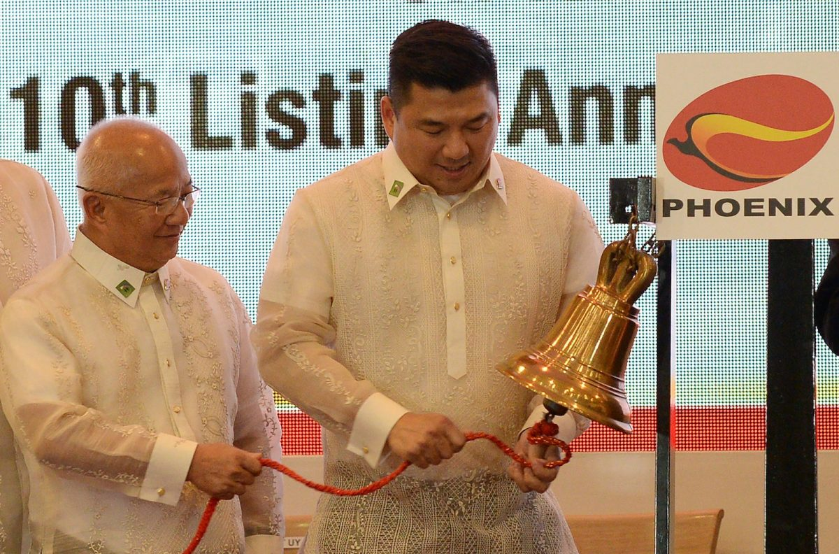 Dennis Uy (R), founder and chief executive officer of Philippines' Phoenix petroleum company, rings the bell at the Philippine Stock Exchange in the financial district of Makati, suburban Manila on July 11, 2017, on the company's tenth anniversary of its listing. Photo: AFP/Ted Aljibe