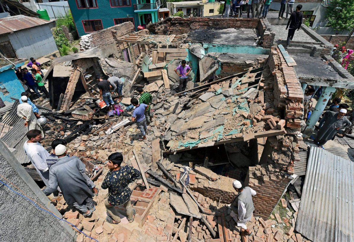 Villagers inspect the ruins of a house that was destroyed during a battle between security forces and militants in Hakhri Pora in Jammu and Kashmir's Pulwama District on Tuesday morning. Photo: PTI