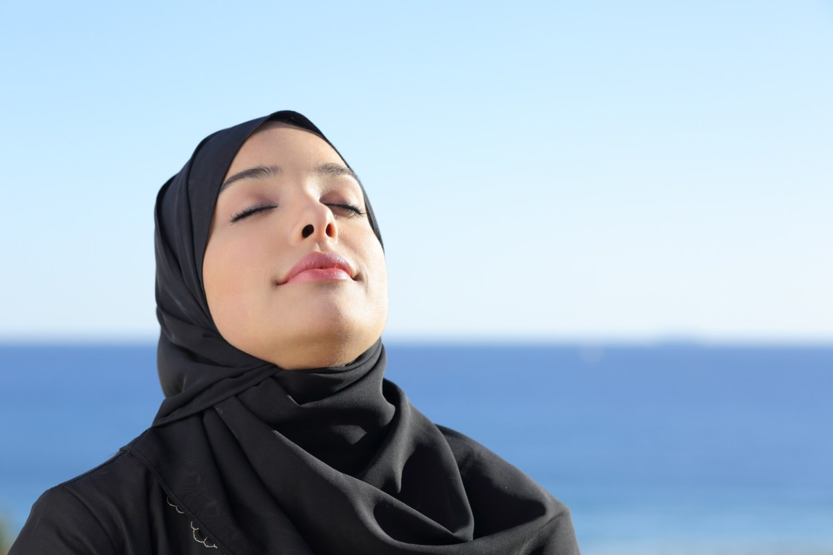 A Saudi Arabian woman in hijab breathes deeply at a local beach. Photo: iStock/Getty Images