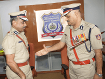 Outgoing Bangalore police commissioner Praveen Sood, right, greets his replacement, T Sunned Kumar. Photo: The Economic Times