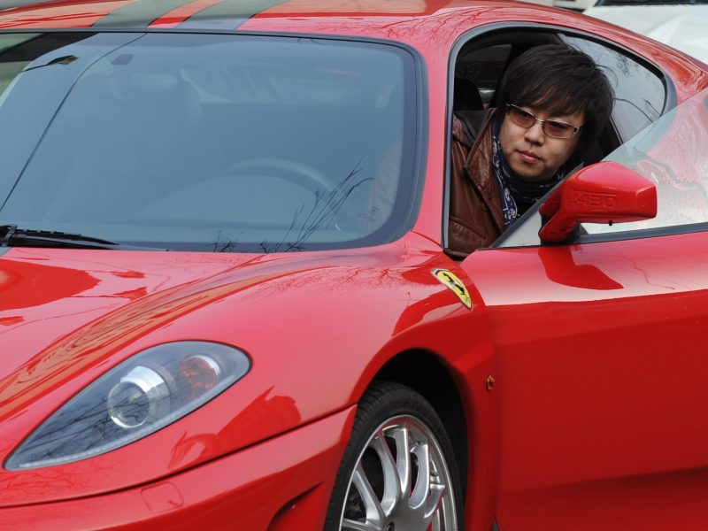 A young Chinese man gets into his Ferrari on a street in Beijing. Photo: AFP / Peter Parks