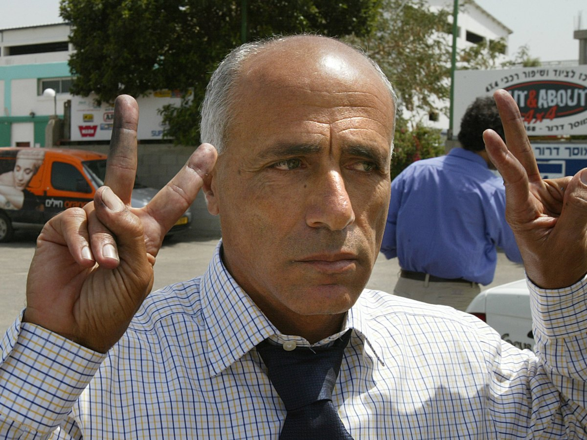 """Former Israeli nuclear technician Mordechai Vanunu flashes the V-sign   after winning his freedom on 21 April 2004. Vanunu said he was """"proud and happy"""" to have blown the whistle on Israel's nuclear program as he was released at the end of an 18-year prison sentence. The one-time technician at the Dimona nuclear plant in southern Israel was abducted by secret service agents in Italy, then smuggled back to Israel and jailed back in 1986 after leaking details of the plant to Britain's Sunday Times newspaper. Photo: AFP / Yoav Lemmer"""