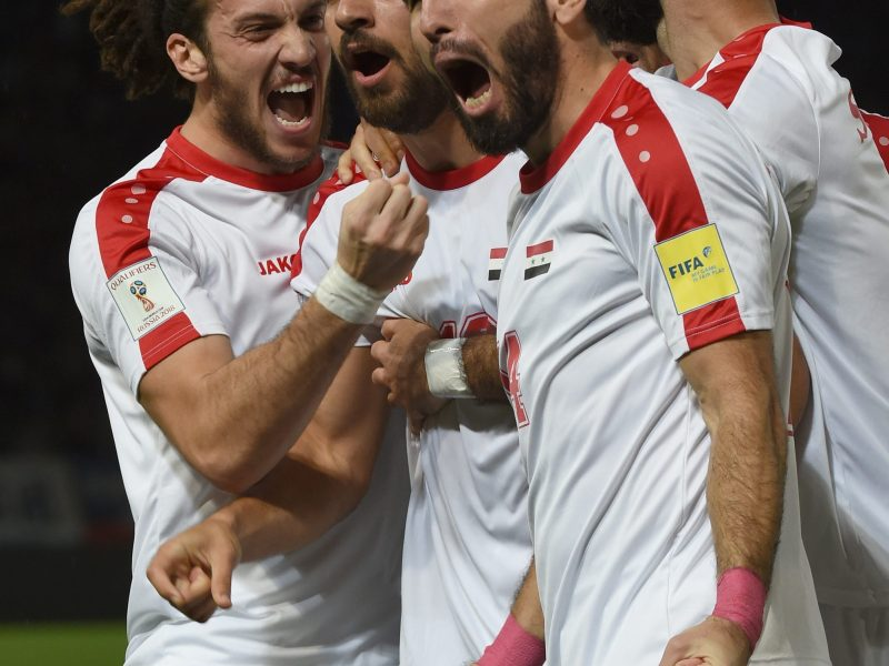 Syrian midfielder Mardik Mardikian (second from left) is mobbed by his teammates after scoring against Japan during a friendly in Tokyo on June 7, 2017. Photo: AFP