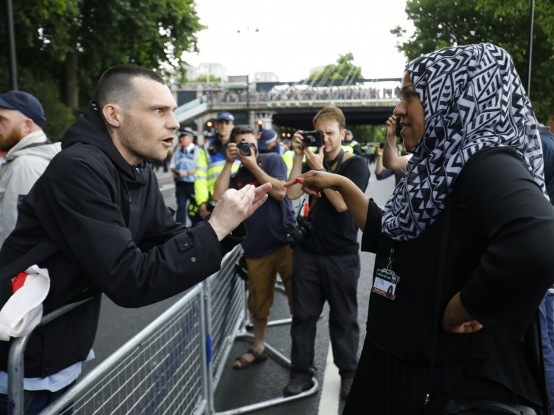 A man gestures at a woman wearing a headscarf during a demonstration organized by the far-right group the English Defence League (EDL) in central London, on June 24, 2017. Photo: AFP /   Tolga Akmen