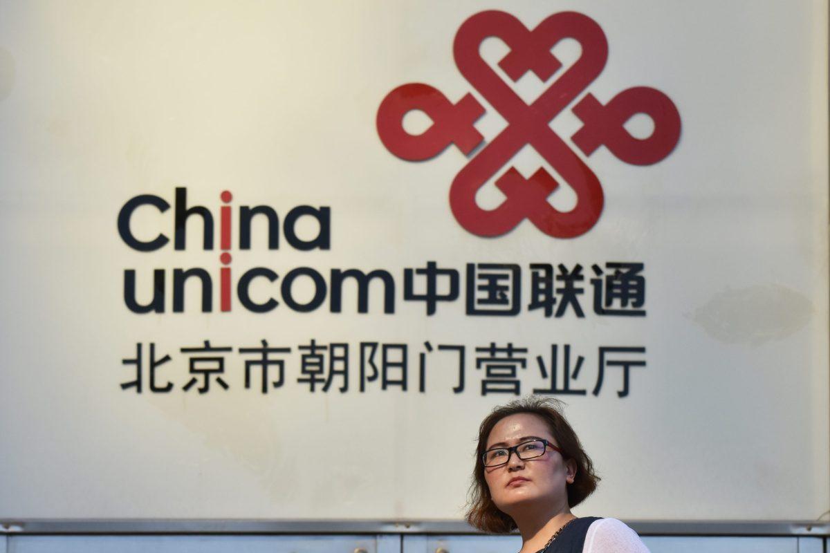 A woman walks past a China Unicom sign in Beijing. Photo: AFP/Greg Baker