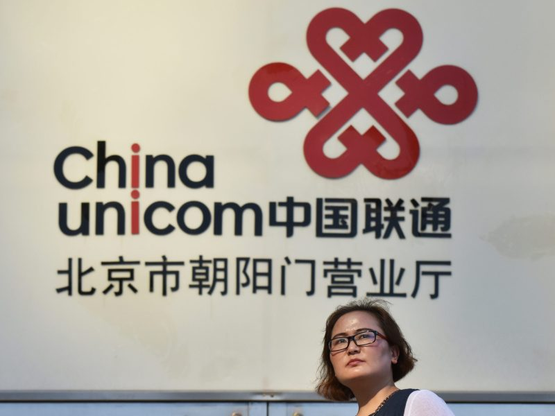 A woman walks past a China Unicom sign in Beijing. Photo: AFP/Greg Baker