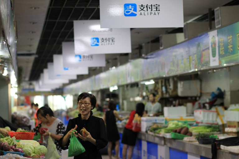 Advertisements for the mobile payment service Alipay of Alibaba Group are seen at a free market in Wenzhou city, east China's Zhejiang. Photo: AFP