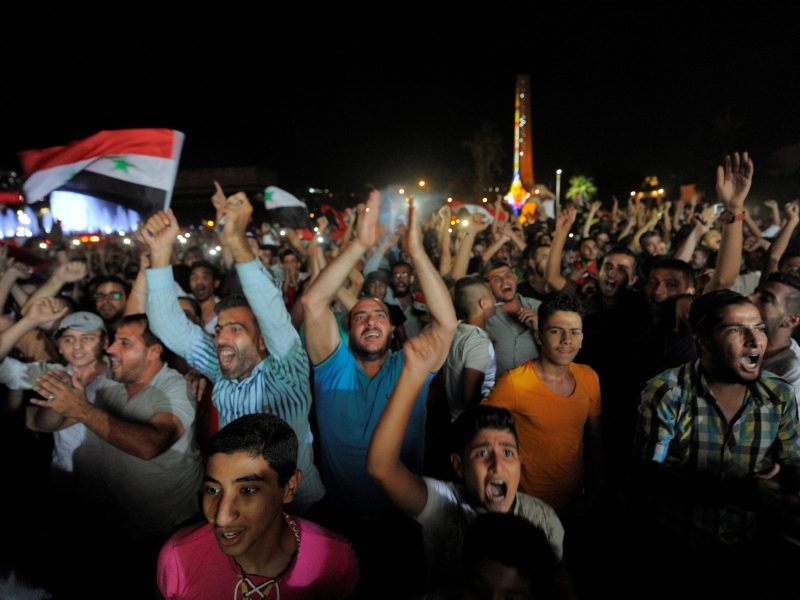 Fans hold Syrian flags as they watch the 2018 World Cup qualifier between Iran and Syria, in Damascus, on September 5, 2017. Photo: Reuters / Omar Sanadiki