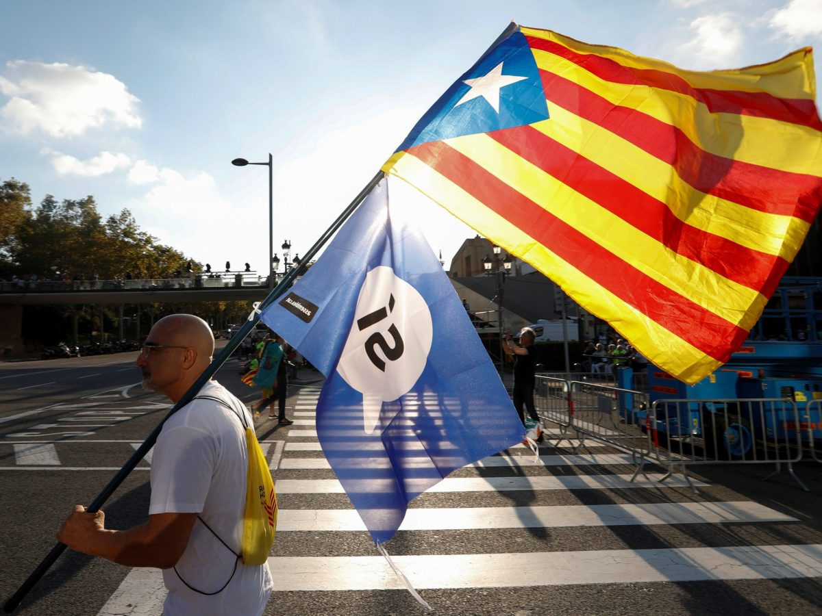 A man holds an Estelada (Catalan separatist flag) and a pro-referendum flag as he arrives at a closing rally in favour of the banned October 1 independence referendum in Barcelona, Spain September 29, 2017. Photo: Reuters/Yves Herman