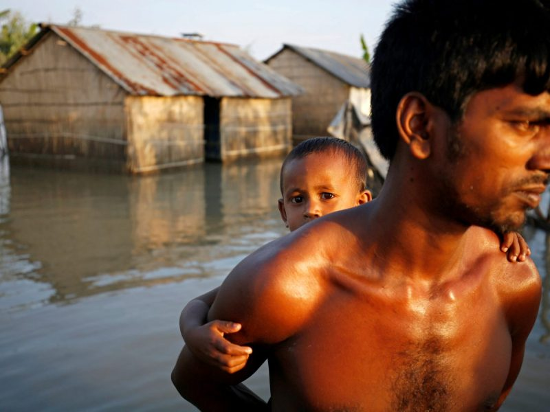 A child reacts to the camera while sitting on his father's back as they make their way in a flooded area in Bogra, Bangladesh, August 20, 2017. Photo: Reuters/Mohammad Ponir Hossain