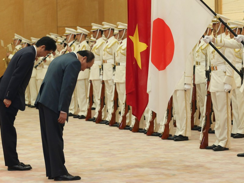Vietnam's Prime Minister Nguyen Xuan Phuc (2nd L) and Japanese Prime Minister Shinzo Abe bow in front of their national flags as they review an honour guard prior to their meeting at Abe's official residence in Tokyo on May 28, 2016.  / AFP PHOTO / POOL / Koji Sasahara