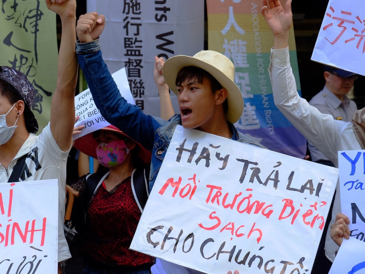 """Vietnamese display placards reading """"Give back the clean ocean to us"""" as they demonstrate outside the Formosa Plastics Corporation headquarters on August 10, 2016.Photo: AFP/ Sam Yeh"""