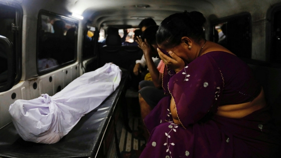 Mother of a stampede victim grieves as she transports her son's body from KEM hospital. (Reuters image)