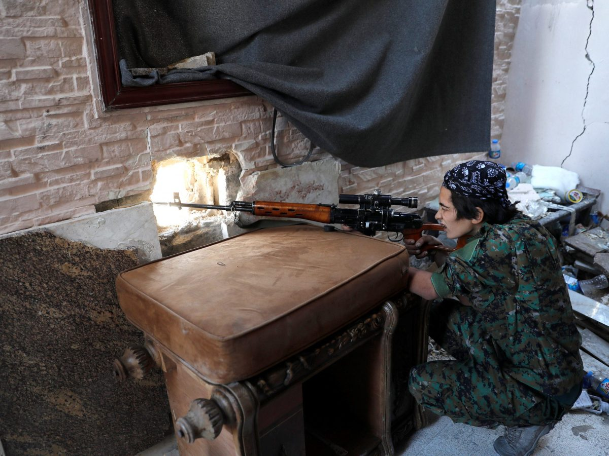 A female Syrian Democratic Forces sniper takes up a position opposite the National Hospital in Raqqa, where Islamic State militants are holed up, on October 16, 2017. Photo: Reuters / Erik De Castro