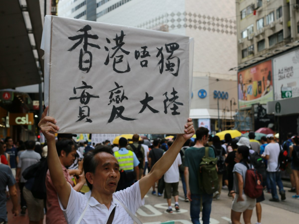 A man holds a a banner saying 'Hong Kong Independence or mainlandization' during a pro-democracy protest in Hong Kong on July 1, 2017. Photo: Asia Times