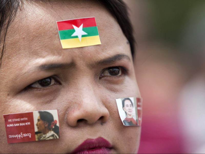 "A woman wears stickers with the image of Myanmar's State Counselor Aung San Suu Kyi on her cheeks as she attends a broadcast of the live speech by Suu Kyi in front of City Hall in Yangon on September 19, 2017. Myanmar leader Aung San Suu Kyi reached out to the global community on September 19 in a broad appeal for support over a refugee crisis the UN has decried as ""ethnic cleansing"", urging outsiders to help her nation unite across religious and ethnic lines and offering a pathway back to the country for some of the Rohingya Muslims forced to flee by army operations. / AFP PHOTO / AUNG Kyaw Htet"