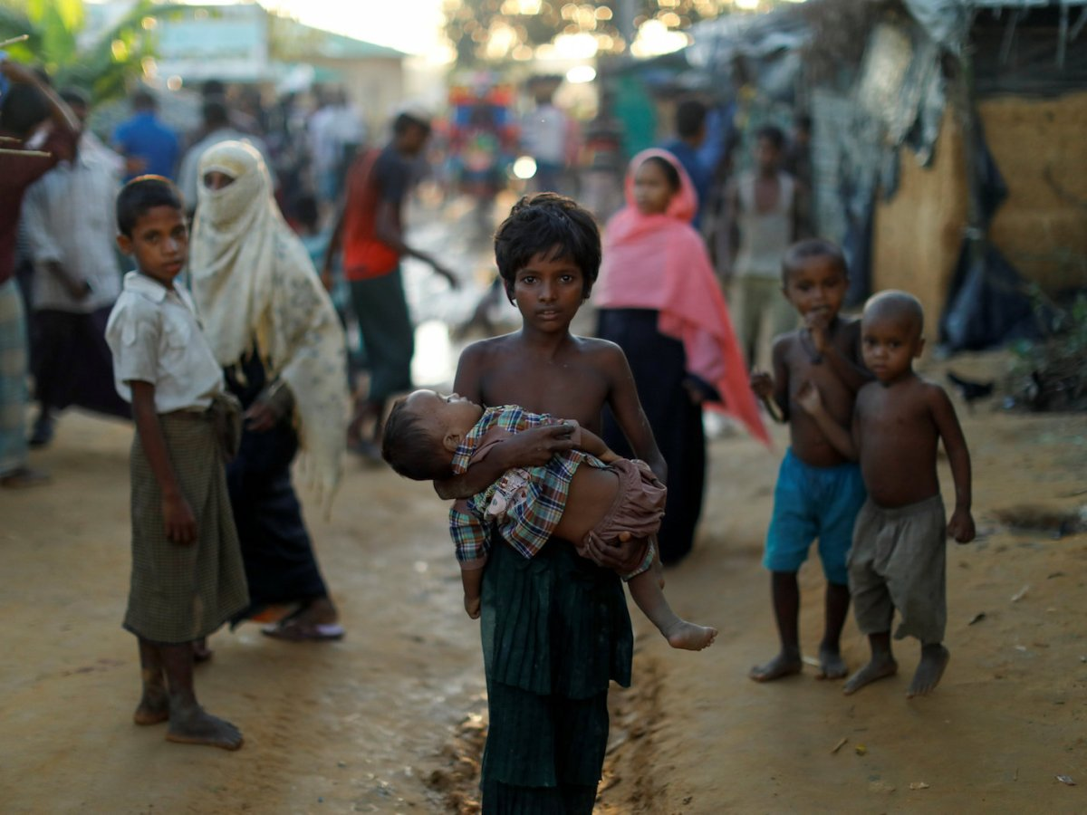 A Rohingya refugee girl carries a baby while walking in a camp near Cox's Bazar, Bangladesh October 10, 2017. : Reuters/Jorge Silva
