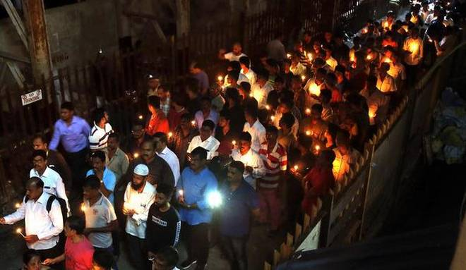 People take part in a candlelight vigil on Monday in memory of those who lost their lives in the stampede on Friday at Mumbai's Elphinstone station.  Photo: The Hindu