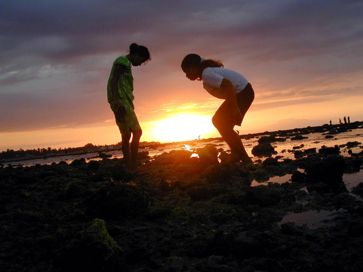 Two Timorese girls look for cockles on the beach in Dili, Timor Leste in a file photo. Photo: AFP/Candido Alves