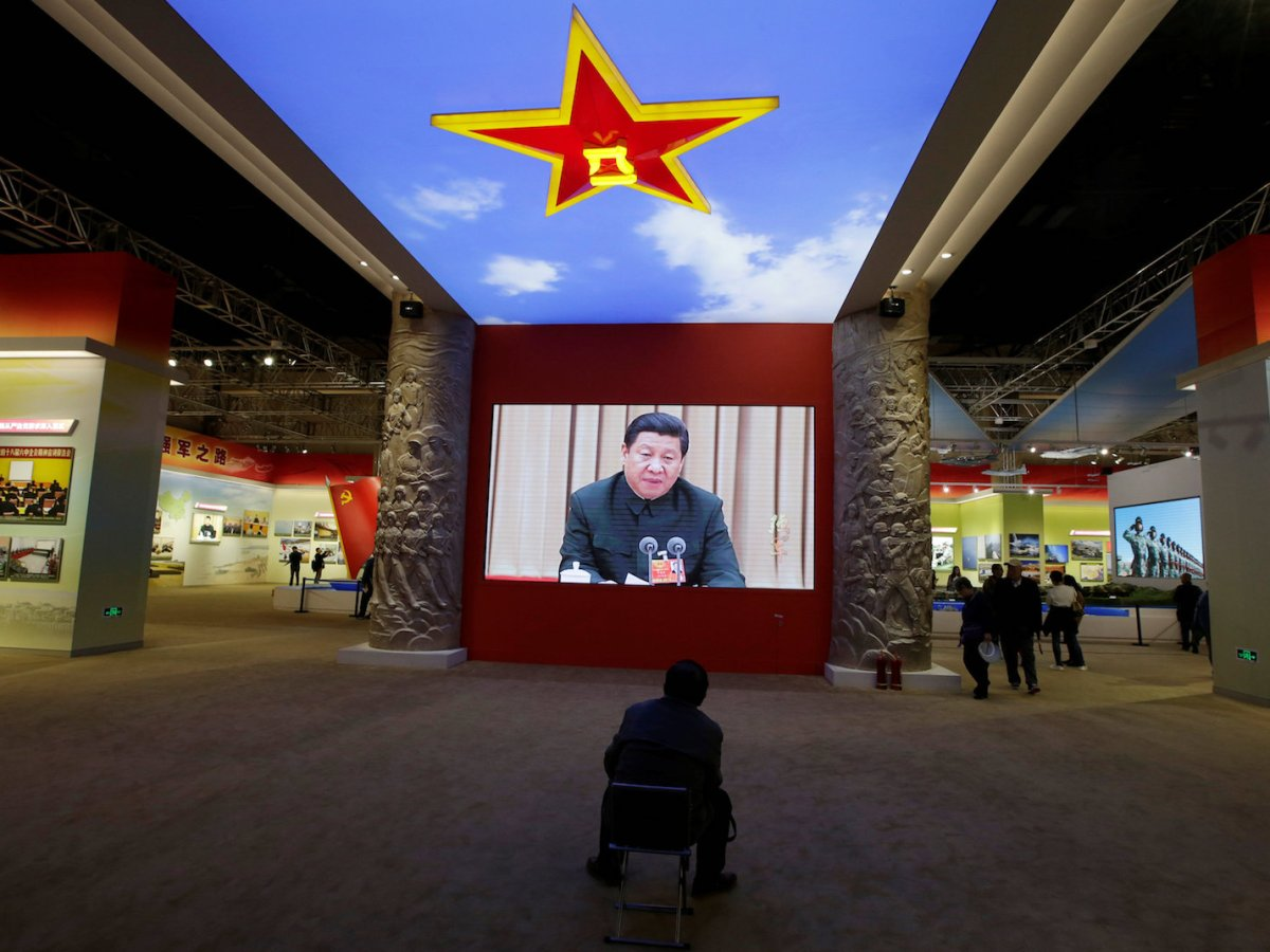 A visitor watches a video of President Xi Jinping talking at an exhibition in Beijing about China's military achievements, on October 10, 2017. Photo: Reuters / Jason Lee