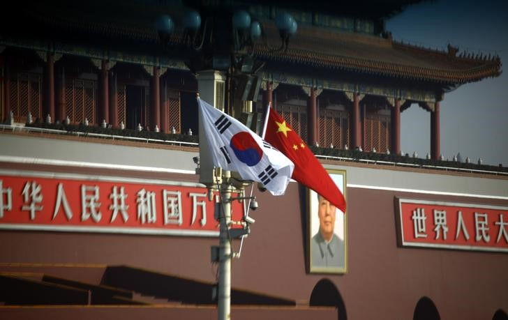 South Korean and Chinese national flags hang from a pole in front of the portrait of former Chinese chairman Mao Zedong at Beijing's Tiananmen Square January. Photo: Reuters/David Gray