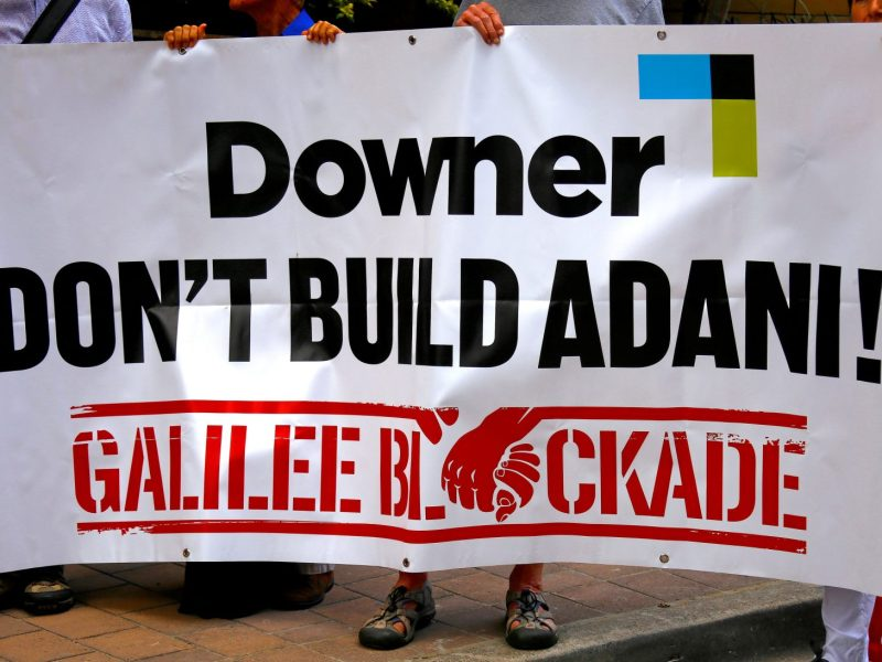 Protesters opposed to the Adani coal project hold a banner outside the venue where mining contractor Downer EDI held its annual general meeting in Sydney on November 2.  Photo: Reuters