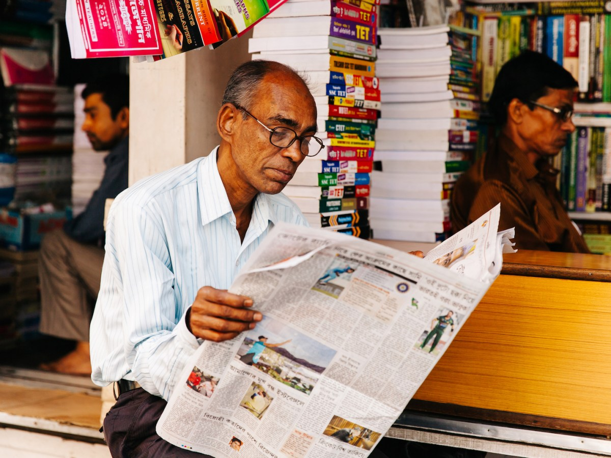 A man reads the morning newspaper at the largest second-hand book market in the world on College Street in Kolkata, India. Photo: iStock