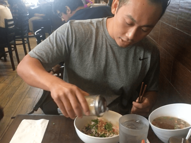 Van Tan tucks into some noodles at Cambodia Town's Phnom Penh Noodle Shack, which he co-owns. Photo: Charley Lanyon